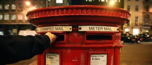 Person posting a letter into a post box