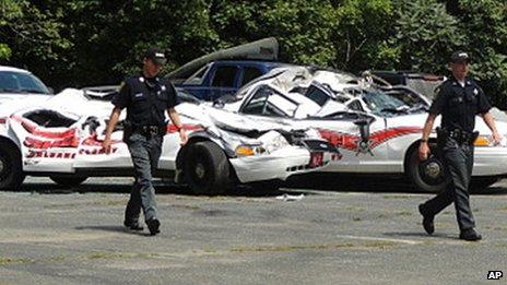 Sheriff officers walk past crushed cruisers at the Orleans County Sheriff&#039;s Department in Newport, Vermont on 2 August 2012