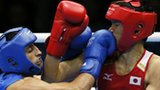 Turkmen boxing referee Ishanguly Meretnyyazov (l) monitors the action between Satoshi Shimizu (r) of Japan and Magomed Abdulhamidov (c) of Azerbaijan