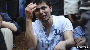A man weeps at a mass burial in Jdeidet Artouz, near Damascus, 1 August