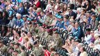 Soldiers sit with spectators in the first day of athletics at the Olympic Stadium