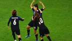 Yuki Ogimi of Japan celebrates with team mates Mizuho Sakaguchi and Homare Sawa  after scoring the opening goal against Brazil