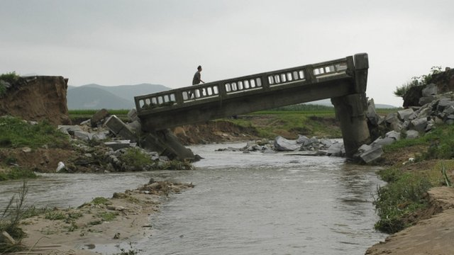 A man walks over a damaged bridge after heavy rain in Onchon County, North Korea