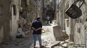 Syrian resident inspects damaged houses after shelling in Qadam, Damascus August 4, 2012