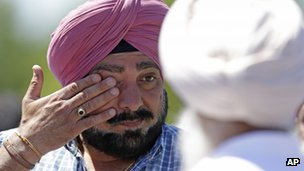 A man wipes away tears outside the Sikh Temple in Oak Creek, Wisconsin, where a shooting took place on 5 August 2012