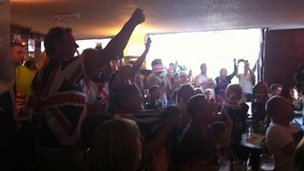 Crowd watching Olympics in pub