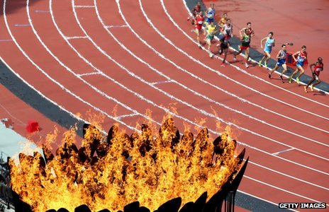 Athletes in steeplechase heats run pas the Olympics cauldron