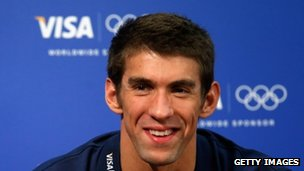 A Visa logo in the background as US swimmer Michael Phelps speaks to the media