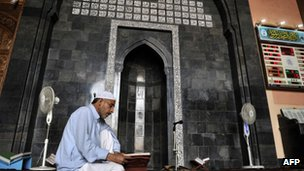 Man reading Koran in mosque in Srinagar
