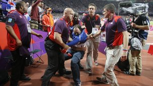 Ashley Gill-Webb is held by security shortly after bottle-throwing incident