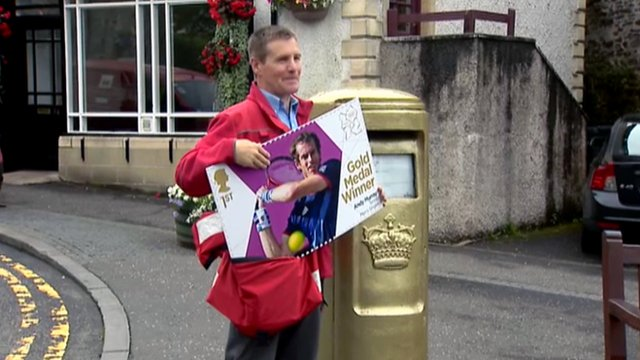 A postman holds a special edition Andy Murray stamp beside the gold post box in Dunblane