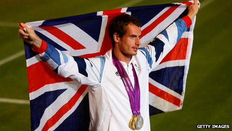 Andy Murray wearing a gold medal and holding up Union Jack flag