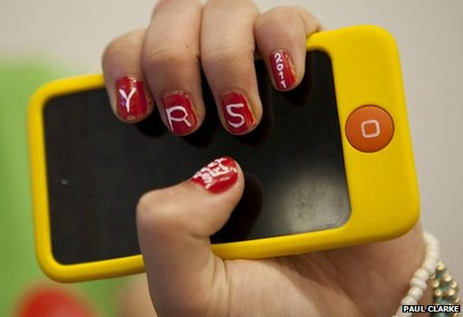 Girl holds up smartphone with Young Rewired State initials painted on her nails