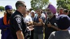 An Oak Creek police officer (L), speaks with members of the Sikh Temple in Oak Creek, Wisconsin August 5, 2012