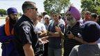 An Oak Creek police officer (L), speaks with members of the Sikh Temple in Oak Creek, Wisconsin August 5, 2012