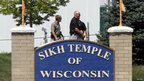Police stand near the Sikh Temple of Wisconsin sign