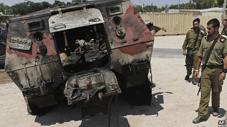 Israeli soldiers stand next to a burnt-out Egyptian armoured personnel carrier captured by gunmen who attacked a border post at Kerem Shalom late on 5 August 2010