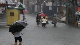 People walking in knee-high water, Manila, 7 August. Photo: Carsten Grevink