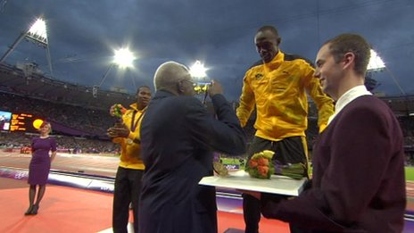 Usain Bolt is presented with a gold medal at London 2012