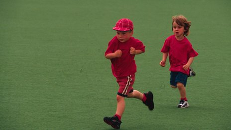 Two children running across school field
