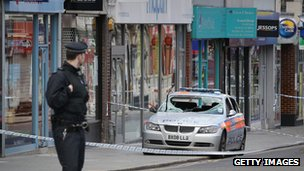 A policeman looks at a damaged patrol car in Church Street, in Enfield, on 8 August 2011, after rioting in London