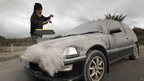 A man sweeps ash off his car near Mount Tongariro