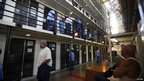 Inmates walk outside their cells at San Quentin state prison