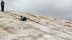 A man slides down a hill after a rare snowfall in Johannesburg, South Africa, on Tuesday 7 August 2012