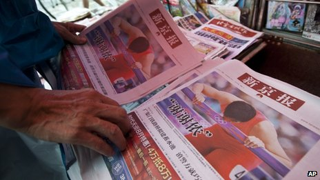 A man picks copies of the Beijing News newspaper at a newsstand, where Chinese hurdler Liu Xiang&#039;s photos are seen on local papers&#039; front pages, in central Beijing, 8 Aug 2012