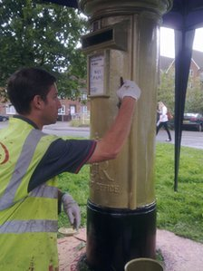 A contract worker painting the postbox in Alton gold for Royal Mail