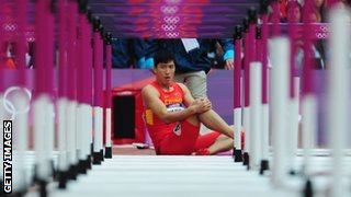 Liu Xiang of China sits on the track after getting injured in the men's 110m hurdles heats