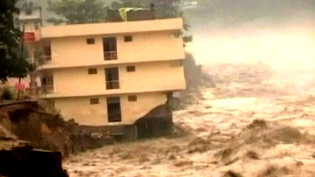 River flowing past partially collapsed housing block in India