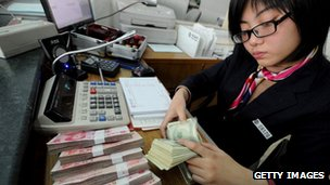 A bank teller counting stacks of US dollars and Chinese 100-yuan notes at a bank in Hefei, east China's Anhui province.
