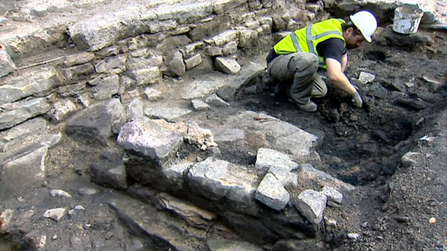 Archaeologist digs remains of houses