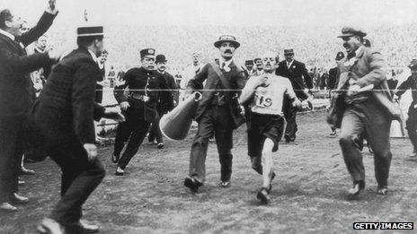 Dorando Pietri of Italy, on the verge of collapse, is helped across the finish line in the marathon event of the Olympic Games in London, 24 July 1908