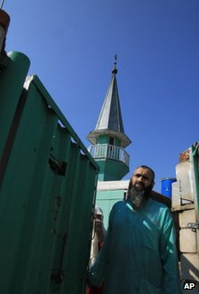 A sect member stands at the gate of their house near Kazan, Russia, 8 August