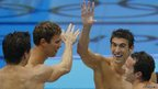 Michael Phelps, second from right, celebrates with team mates