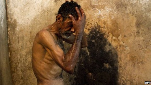 A heroin addict showers takes a shower at the Edhi rehabilitation centre in Karachi