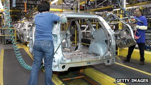 Workers build a GM crossover SUV as it goes through the assembly line at the General Motors