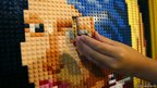 A girl makes up a picture with Lego