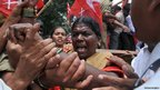 Indian police detain a woman during a protest