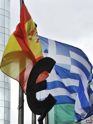 The Spanish and Greek flags fly behind a statue of the euro sign in front of the European Parliament in Brussels