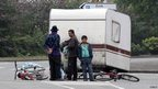 Roma men stand next to a caravan in the street as they are evicted from an illegal camp in Villeneuve d'Ascq, northern France