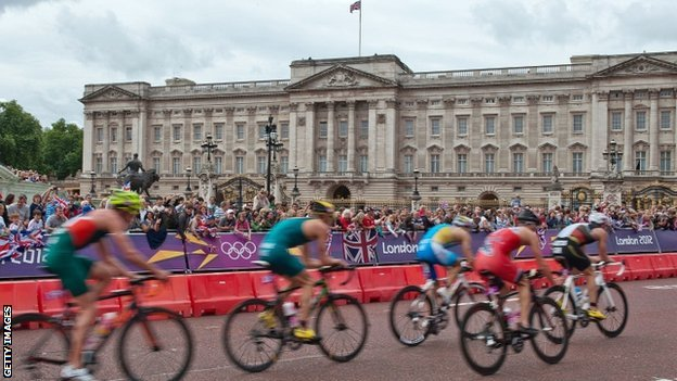 The men's triathlon race cycles past Buckingham Palace