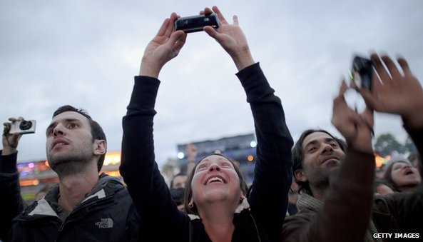 Festival-goers use their mobile phones and cameras to record a Portishead concert