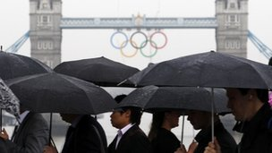Commuters walk across London Bridge, as Tower Bridge adorned with the Olympic rings