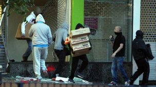 Looters leave an electronics store in Birmingham
