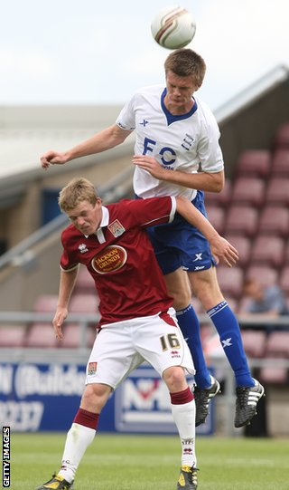 Kerr rises above Northampton Town's Billy McKay during pre-season
