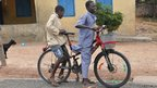 Children on a bicycle with a red ribbon in Accra, Ghana