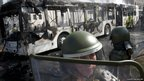 Chilean riot police members stand next to a burned-out bus
